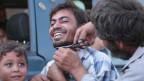 Ein Mann lässt sich nach der Befreiung in Manbidisch den Bart schneiden.