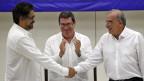 Der Delegationschef der Farc, Iván Márquez (links), reicht dem Verhandlungsführer der Regierung, Humberto de la Calle, die Hand. In der Mitte, Kubas Aussenminister Bruno Rodriquez.
