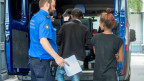 Ein Grenzwächter begleitet, am Bahnhof in Chiasso Flüchtlinge. Sie wollten mit einem Bus nach Deutschland gelangen, konnten aber an der Schweizer Grenze nicht weiterreisen, da sie keinen Pass besassen. Archivaufnahme vom Juli 2016.