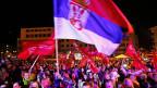 Eine bosnische Flagge weht über der Menschenmenge, die der Rede von Milorad Dodik in Pale zuhört.
