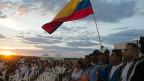 Während einer LIVE-Übertragung der Feier zur Unterzeichnung des Friedensvertrags zwischen Regierung und FARC-Rebellen umarmen sich Männer und Frauen im Süden des Landes und schwenken eine kolumbianische Flagge.
