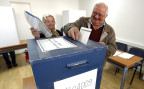 Ein älteres bosnisches Ehepaar gibt ihre Stimmen ab in einem Wahllokal in Sarajewo.