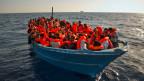 Dichtgedrängt sitzen Migranten und Migrantinnen aus Somalia und Eritrea in einem Flüchtlingsboot nahe der libyschen Küste.