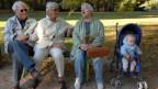 Drei Rentner sitzen auf einer Bank. Neben ihnen ein Kleinkind im Kinderwagen.