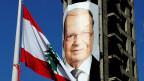 Die libanesische Flagge mit der Zeder weht vor einem Wahlplakat mit dem Bild von Michel Aoun.