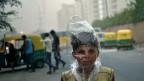 In einer Strasse von Delhi herrscht dichter Smog; ein kleiner Junge hat sich als Schutz vor der schlechten Luft einen Plasticsack über den Kopf gezogen.
