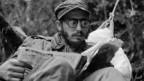 Der junge Fidel Castro, in der Sierra Maestra sitzend mit einer Brille, ist in eine Lektüre vertieft.