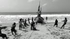 Fischer ziehen in Totope an der westafrikanischen Küste in Ghana ein traditionelles Fischerboot auf den Strand.