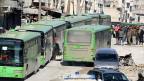 Menschen versammeln sich im Osten Aleppos bei den Bussen, mit denen sie aus der Stadt gebracht werden sollen.