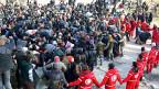 Mitglieder des regionalen Roten Kreuzes bilden einen Kreis um eine Gruppe Menschen, die aus Ost-Aleppo evakuiert werden sollen.