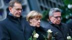 Der Berliner Bürgermeister Michael Müller, Bundeskanzlerin Angela Merkel undInnenminister Thomas de Maizière bei einer Schweigeminute auf dem Berliner Weihnachtsmarkt in der Nähe der Gedächtniskirche.