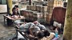 Am Rande der Markthalle im Slum auf der philippinischen Insel Cebu schläft ein junges Paar eng aneinander geschmiegt auf einem Feldbett.