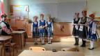 Auch nach 20 Berufsjahren ist Primarlehrerin Tanya Lubenova noch begeistert von der kindlichen Energie und Neugier. Verzaubert schaut sie den Schülerinnen zu, die den Schweizer Journalisten mit traditionellen Liedern und Tänzen begrüssen.