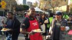Policeofficer Deon Joseph hat sich eine rote Schürze über seine Uniform gebunden und hilft bei der Essensausgabe mit.