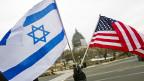Ein pro-israelische Demonstrant schwenkt je eine Flagge Israels und der USA vor dem Capitol in Washington.
