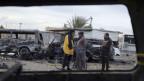 Durch ein Fenster in einem ausgebrannten Auto sieht man drei Männer, die zwischen ausgebrannten Fahrzeugen stehen.