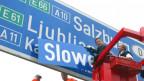 Jörg Haider steht auf einem Hebekran und wechelt die Beschriftung auf einer blauen Autobahntafel aus, aus «Ljubliana» wird «Slowenien» (2002).
