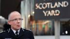 Uniformierter Mann mit Brille steht vor Schriftzug Scotland Yard