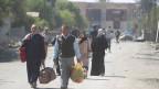 Vertriebene Iraker fliehen mit ihren Habseligkeiten aus ihren Häusern in Mossul.