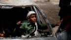 Ein Junge spielt in einem zerbombten Auto im Hof der Al-Shawkani-Stiftung für Waisenpflege in Sanaa, Jemen.