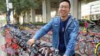 Liu Zhengyang leiht ein Mobike aus. Mobike-Velos sind mit GPS ausgestattet. Das Unternehmen weiss deshalb, wo sich die Fahrräder befinden, und berechnet den Kunden die Kosten für die Dauer der Fahrt.
