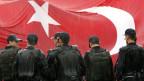 Beamte vor grosser Türkeiflagge.