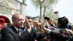 Der Türkische Präsident Erdogan grüsst seine Anhänger vor einer Moschee in Istanbul.