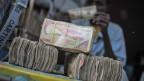 Ein Bündel Banknoten, im Hintergrund ein Mann beim Geldzählen.