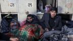 Migranten in Decken in einem verfallenen Zolllager in Belgrad, Serbien.