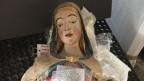 Der Madonna fehlen die Arme. Sie liegt auf einen Schaumstoffkissen, das aussieht als wär's ein Krankenbett.