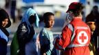 Eine Mitarbeiterin des italienischen Roten Kreuzes betreut neu angekommene Flüchtlinge.