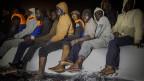 Afrikanische Flüchtlinge versuchen, auf einem überfüllten Schlauchboot nach Libyen zu gelangen.
