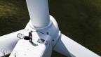 Ein Mann steht für Instandhaltungsarbeiten auf einer Windkraftanlage am Mont-Soleil in Saint-Imier