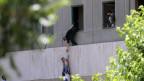 Iranische Polizisten versuchen, Zivilisten zu helfen, aus dem Parlamentsgebäude zu fliehen während des Angriffs in Teheran am 7. Juni 2017.