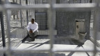 Ein Gefangner im kalifornischen Gefängnis San Quentin sitzt in einem Käfig im Innenhof, er ist schwarz, trägt graue Hosen und einen weissen Pulli, dazu eine Sonnenbrille, neben ihm ist eine WC-Schüssel.