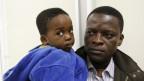 Hoffen auf Asyl: Ein afrikanischer Vater mit seinem Sohn bei der Ankunft in Italien.