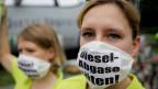 Diesel sollen mit neuer Software sauberer werden. Bild: Demonstrantin gegen Dieselfahrzeuge.