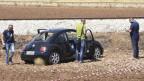 Zu sehen sind Polizisten, die in einem Auto ein Opfer der Bluttat vom Mittwoch in der Provinz Foggia in Apulien entdecken.