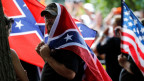 Ein Mitglied des Ku Klux Klans mit der Flagge der US-Südstaaten.