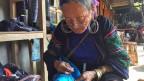 Die Frauen und Mädchen sind Angehörige des Stammes der Black Hmong, die den Touristen Batikkurse anbieten.