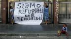 Nach der Hausräumung in Rom hängen Flüchtlinge ein Transparent auf.