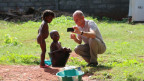 Patrik Wülser zeigt lachenden Kindern Fotos.