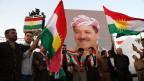 Kurdische Männer mit einem Portrait von Masaud Barzani, dem Präsidenten der kurdischen Autonomiezone.