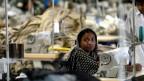 Eine Arbeiterin in einer Textilfabrik in Bangladesch, sie sitzt in traditioneller Kleidung mit Kopftuch vor einer Nähmaschine, im Hintergrund noch mehr Maschinen, Spulen und Stoffe.