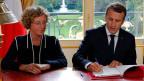 Der französische Präsident Emmanuel Macron unterzeichnet eine neue Verordnung. Links ist Arbeitsministerin Muriel Penicaud.