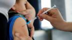 Ein kleines Kind wird von einer Ärztin geimpft.