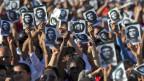 Viele Menschen halten ein schwarz/weiss Bild von Che Guevara in die Luft.