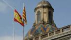 Die spanische und die katalanische Flaggen wehen auf dem Regierungsgebäude in Barcelona.