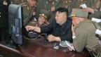 Der nordkoreanische Diktator Kim Jong-un schaut sich mit Artillerie-Soldaten zusammen einen Computer an.