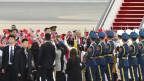 Das Bild zeigt US-Präsident Donald Trump inmitten von Soldaten bei der Ankunft in China.